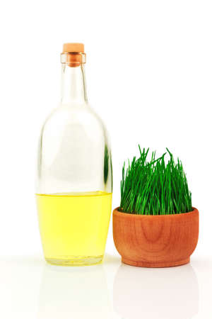 Glass transparent bottle and fresh sprouts of wheat in wooden bowl isolated on white background Reklamní fotografie
