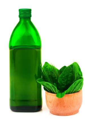 Glass green bottle and fresh herbs in wooden bowl and isolated on white background