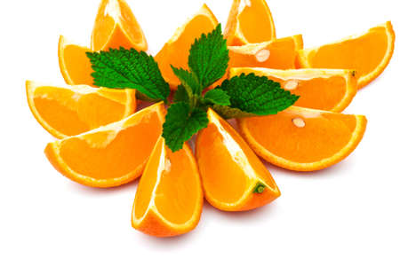 Macro view of orange with slices and fresh green leaf of mint on white background