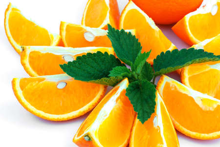 Macro view of orange with sections and fresh green leaf of mint on white background Reklamní fotografie