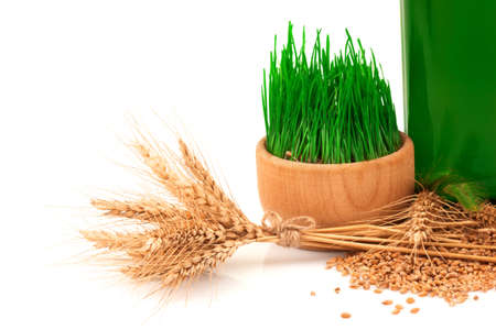 Macro view of glass green bottle with oil, sprouts of wheat in wooden bowl and ears of wheat with burlap tied isolated on white background Reklamní fotografie