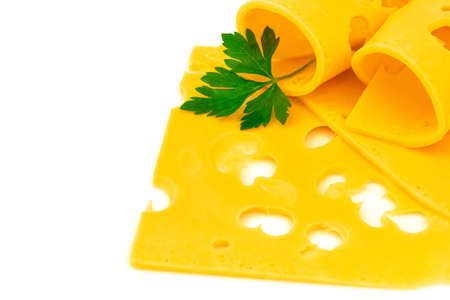 Macro view of rolled thin slices of hard yellow cheese with holes and fresh parsley on white background