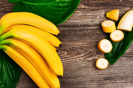 Macro view of bunch of fresh raw organic yellow bananas with slices and green leaves on wooden background
