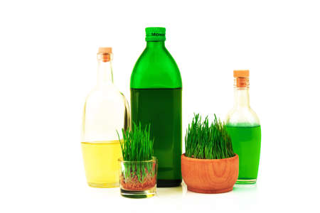 Glass bottles with oil and juice and fresh sprouts of wheat in wooden bowl isolated on white background