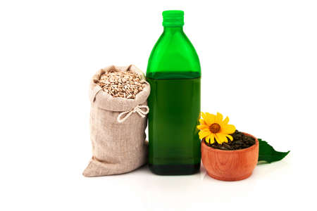 Sunflower oil in glass bottle, sunflower seeds in sack and rustic wooden bowl with fresh flower and leaves on white background Reklamní fotografie