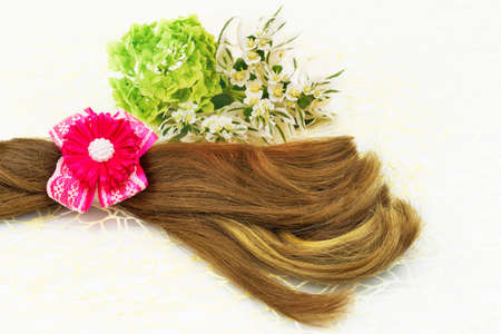 Hair and barrette with pink ribbon, white flowers and green leaf on white lace background. Reklamní fotografie