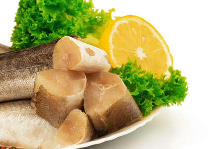Macro view of raw slices of fish hake, pollock on the plate with lemon and leaves of salad lettuce isolated on white background.
