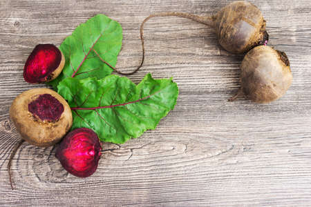 Top view at fresh organic beets with leaves on wooden rustic table background. Close up view.
