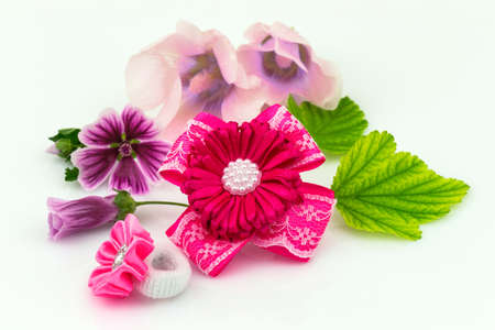 Barrette with ribbon and elastic, natural flowers and green leaf isolated on white background.