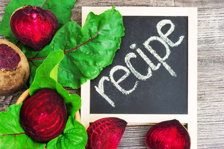 Top view at fresh organic beets with leaves with recipe on wooden rustic table background. Close up view.