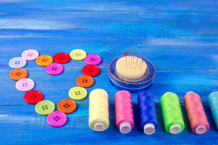 Multi colored buttons and threads, Laid out in the form of a heart, as well as pins on a blue wooden background.