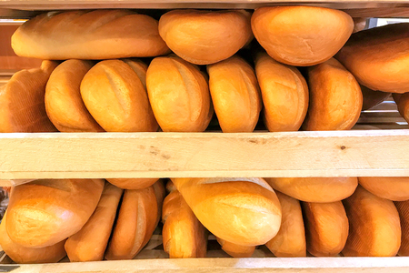 bakery products: Fresh wheat bread on shelves in store. Many of bread on racks. Stock Photo
