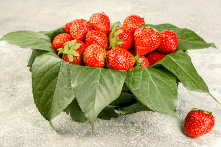 Ripe strawberries in a basket decorated with leaves on a gray background. The concept of a generous summer harvest of berries. Close-up.