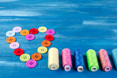 well laid: Multi colored buttons and threads, Laid out in the form of a heart, as well as pins on a blue wooden background. Close-up. Stock Photo