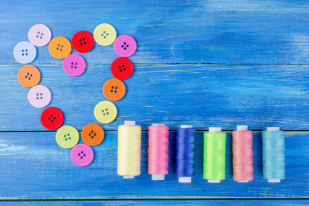well laid: Multi colored buttons and threads, Laid out in the form of a heart, as well as pins on a blue wooden background. Top view. Flat viev. Close-up.