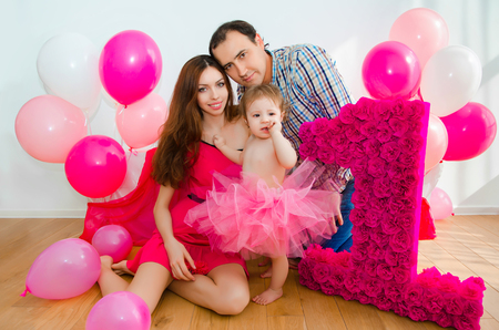 first birthday: Family celebrating first birthday of baby daughter.little girl in pink skirt with Mom and Dad.
