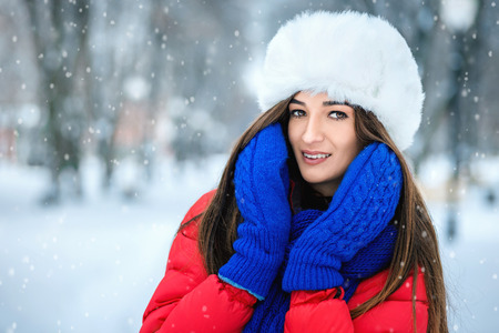 A girl in a white fur hat covers her face with her hands dressed in blue mittens.