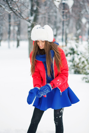 Attractive young woman in wintertime outdoor. Cheerful girl wears blue mittens. Stock Photo