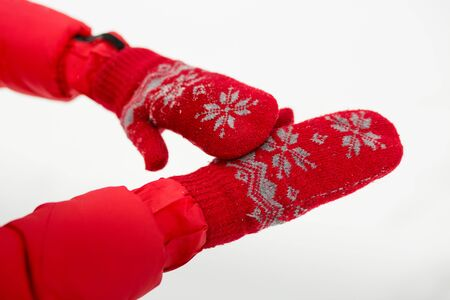 Female hand in red mittens with snow.