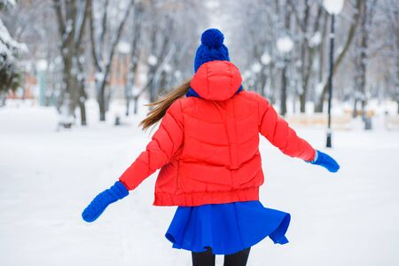 winter dance: Beautiful winter Portrait of a young woman in winter snow-covered landscape. The girl whirls into a fun dance. Stock Photo