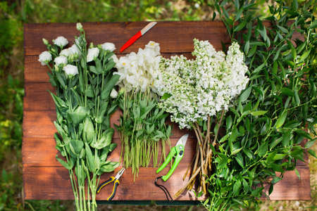 floristry: White flowers on a wooden table. View from above. Gardening and floristry, preparation of flowers to create a bouquet.
