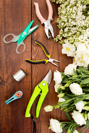 floristry: Garden tools, Tools for floristics and flowers on a wooden table. Gardening and floristry, preparation of flowers to create a bouquet.