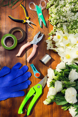 Garden tools, Tools for floristics and flowers on a wooden table. Gardening and floristry, preparation of flowers to create a bouquet.