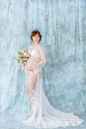 negligee: Pregnant woman holding flowers, standing in the boudoir dress (negligee) on a blue background. whole-length.
