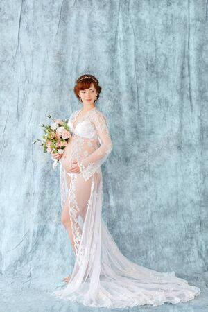 luz natural: La mujer embarazada con flores, permanente en el vestido boudoir (salto de cama) sobre un fondo azul. longitud entera Foto de archivo