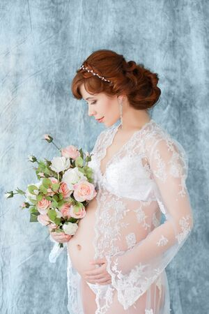 negligee: Pregnant woman holding flowers, standing in the boudoir dress (negligee) on a blue background. Stock Photo