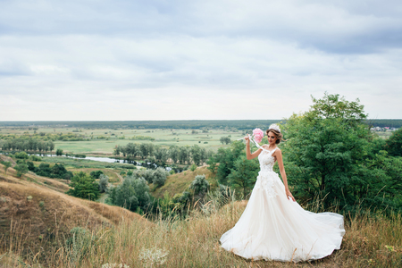 Beautiful young bride girl smiling, standing in wedding dress. Overlooking the beautiful green valley with a river.