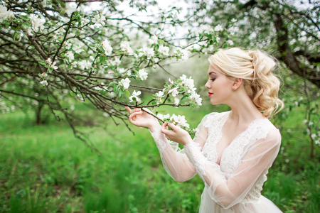 Portrait of a young girl, the bride in the apple orchard. Beauty wedding hairstyle. Bride. Beautiful hairstyle rear view. Young beautiful blonde woman in blooming garden.