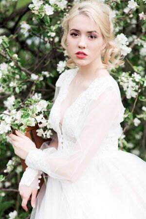 Portrait of a young girl, the bride in the apple orchard. Wedding hairstyle make-up luxury wedding dress and brides bouquet. Stock Photo