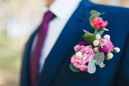 Grooms boutonniere of pink and red roses on a blue suit Wedding details.
