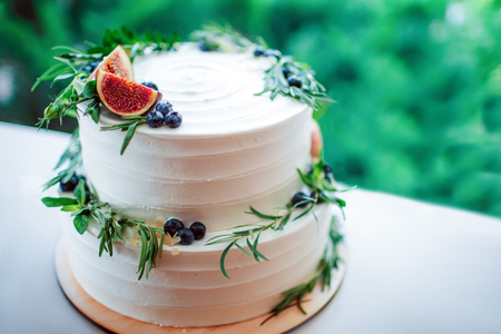 Wedding white cake with figs and raspberries. Rustic wedding cake decorated with figs, blueberries and greenery rosemary. Stock Photo