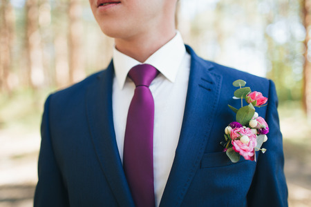 Groom's boutonniere of pink and red roses on a blue suit Wedding details. 스톡 콘텐츠