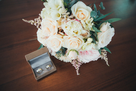 Classic wedding gold rings of the bride and groom on a table, with a beautiful wedding bouquet of flowers of the bride. Wedding rings newlyweds.