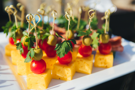 Assorted mini canapes closeup, delicacies and snacks, restaurant food at event. Decorated delicious table for a party goodies. Imagens