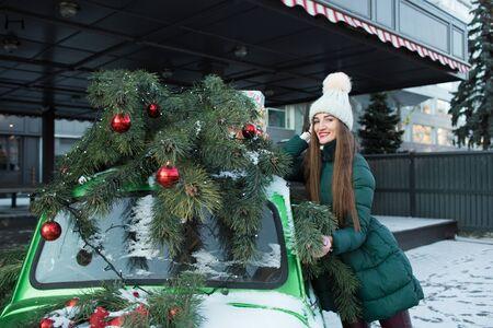 Ragazza in abiti verdi invernali per strada, vicino a un'auto retrò verde. Bella donna felice con confezione regalo alla festa. Vacanze di Natale e Capodanno.