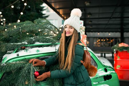 Girl in winter green clothes on the street, near a green retro car. Beautiful happy woman with gift box at celebration party. Christmas and New Year holidays.