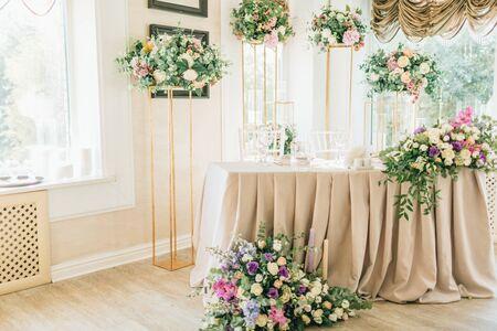 Blumenhochzeitsdekoration. Hochzeitstafel mit frischen Blumen dekoriert. Hochzeitsfloristik. Bouquet mit Rosen, Eustoma und Eukalyptusblättern.