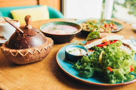 Vegan and vegetarian food. Variety of dishes on a wooden table, top view, flat lay, kitchen items. Banco de Imagens