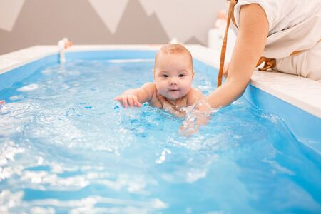 Litle baby in pool swimming bathing during health procedures. Child swims in the hands of the instructor.
