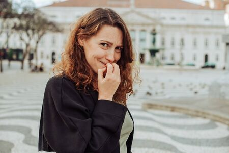 Closeup portrait unsure hesitant portuguese woman biting her fingernails craving for something or anxious shot in Lisbon, Portugal. Negative human emotions facial expression or bad habit concept