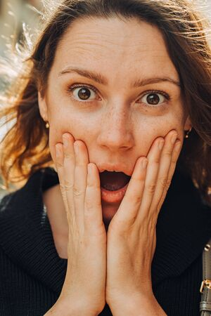 Close up headshot portrait of a young caucasian woman with freckles closing mouth with hands and eyes wide open. Human emotions, facial expression of fear, amazement, astonishment or admiration