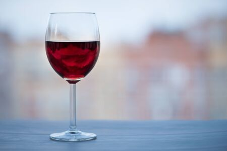 A glass of red wine near the window on a wooden table