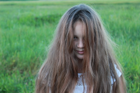 Girl with loose shaggy hair in nature Stock Photo