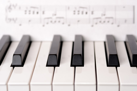 Close-up piano keyboard. Sheet music on background is copyright free (Wolfgang Amadeus Mozart).