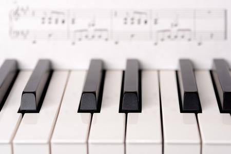 sheet music background: Close-up piano keyboard. Sheet music on background is copyright free (Wolfgang Amadeus Mozart).