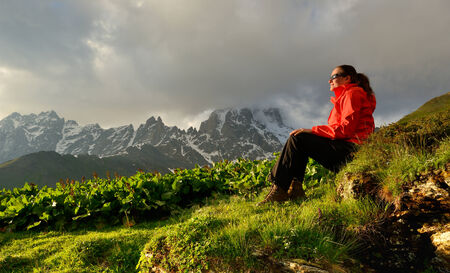 Young woman in red jacket enjoy sunset in mountains photo